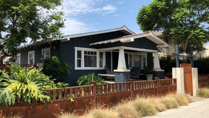 dark blue bungalow style home on a sunny street behind a low, wooden fence
